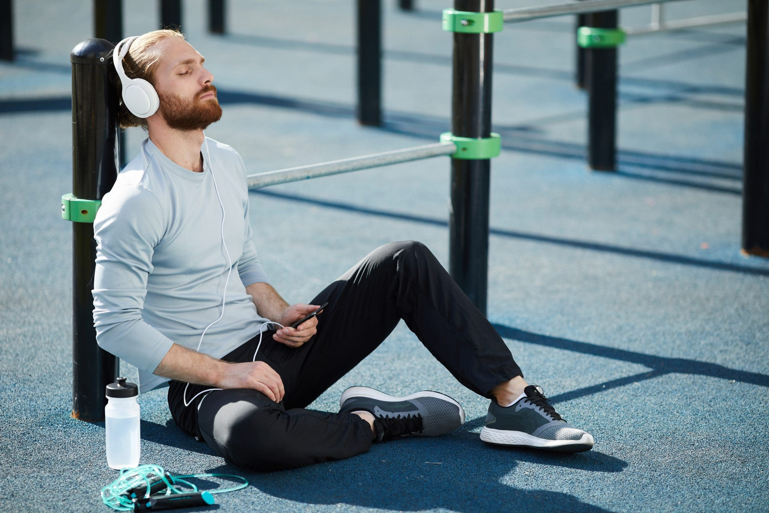 Calm relaxed young bearded man in headphones sitting on sports ground and keeping eyes closed while meditating before training