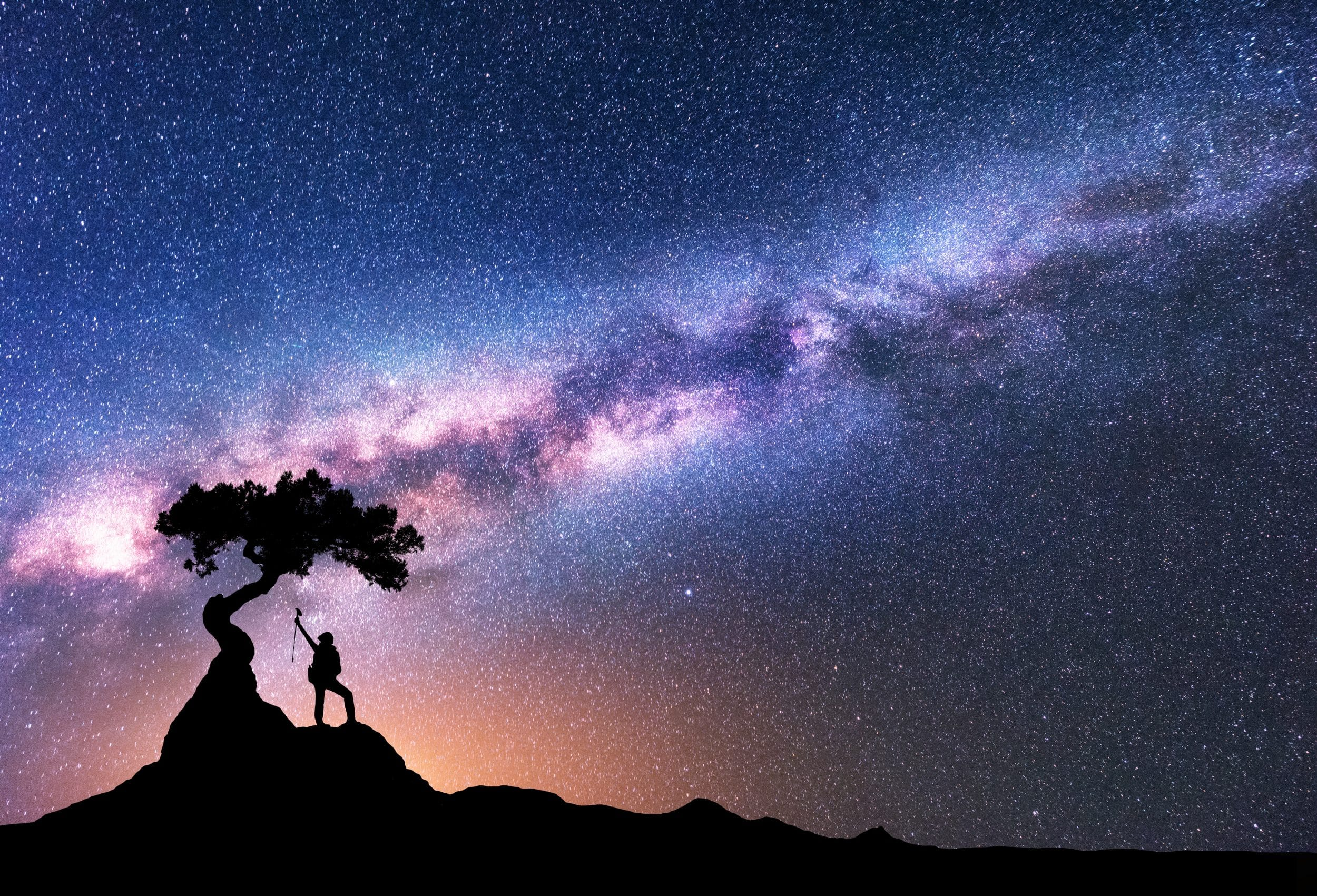 Milky Way and silhouette of woman under the tree growing from the rock on the mountain at night. Space background with starry sky, beautiful galaxy and girl. Purple Milky Way and woman. Universe