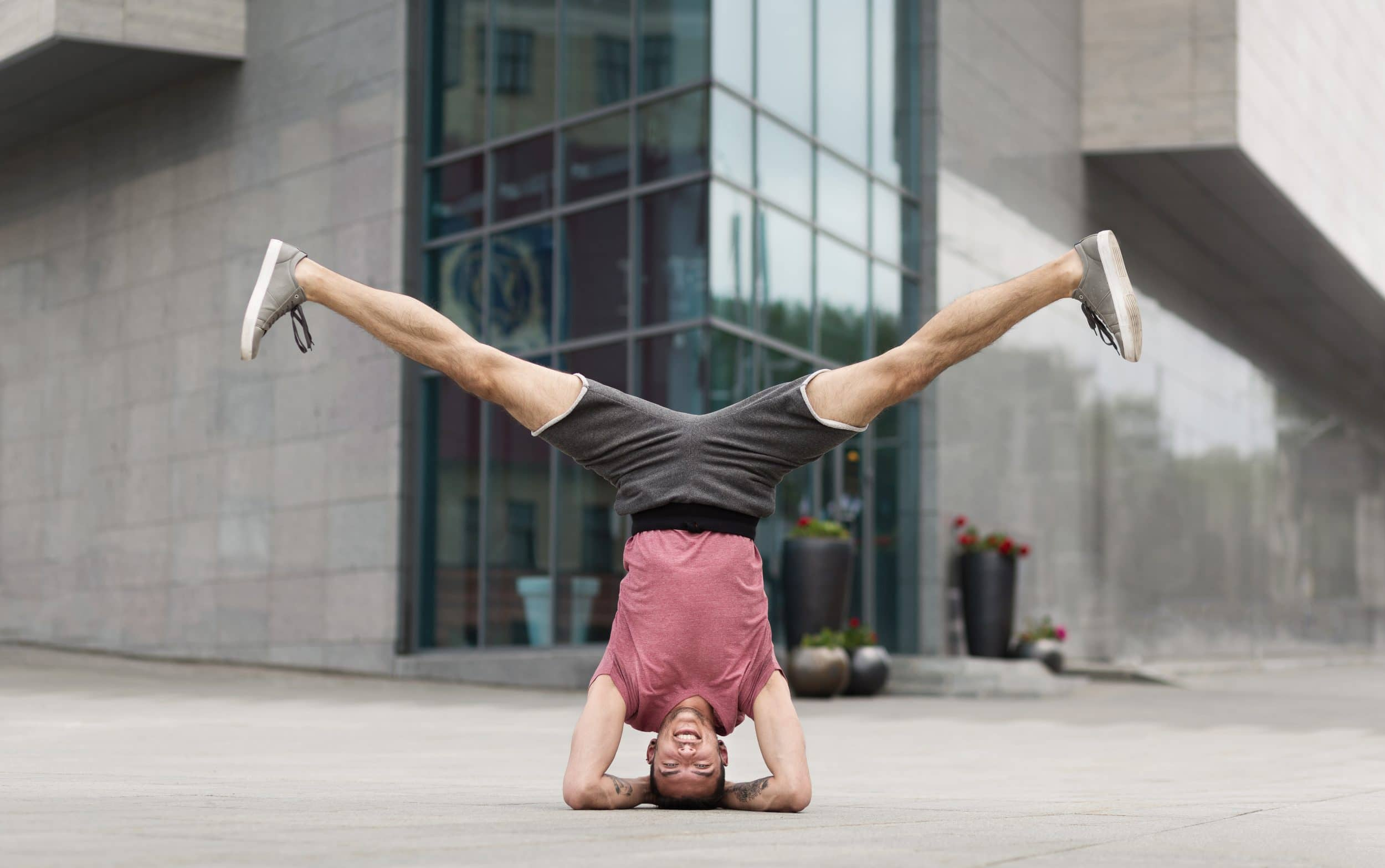 Young man doing yoga headstand exercise on building background